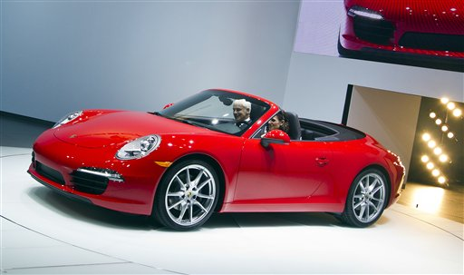 Porsche AG President and CEO Matthias Müller is driven out in the 2013 911 Cabrio convertible, at the North American International Auto Show, Monday, Jan. 9, 2012, in Detroit, Mich. (AP Photo/Tony Ding)<br />