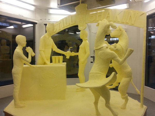 "A 1,000 pound work of art featuring two dancing cows next to three human beings drinking milkshakes is made entirely out of butter. Its theme is ""Shake, Rattle and Roll,"" which is a hit song from 1954 — coincidentally, the same year the Farm Show unveiled its now-famous milkshake. (Courtesy of Mid-Atlantic Dairy Association)"