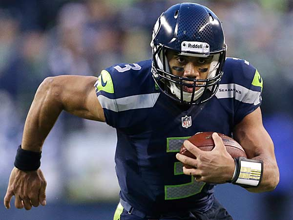 Seattle Seahawks quarterback Russell Wilson keeps the ball and rushes for a 15-yard gain in the second half of an NFL football game, Sunday, Dec. 30, 2012, in Seattle. The Seahawks won 20-13. (Elaine Thompson/AP)