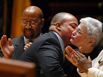 As Mayor Michael Nutter (left) applauds, Seth William kisses outgoing D.A. Lynne M. Abraham (right) immediately after he was sworn in as her replacement Monday. (Tom Gralish / Staff Photographer)