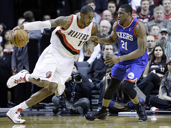 Trail Blazers forward LaMarcus Aldridge, left, drives on 76ers forward Thaddeus Young during the first half. (Don Ryan/AP)