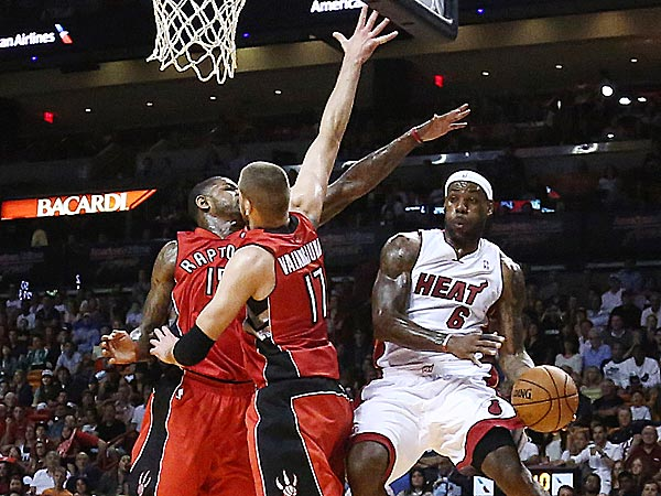 Raptors defenders Amir Johnson and Jonas Valanciunas try to block the Heat´s LeBron James. (J Pat Carter/AP)
