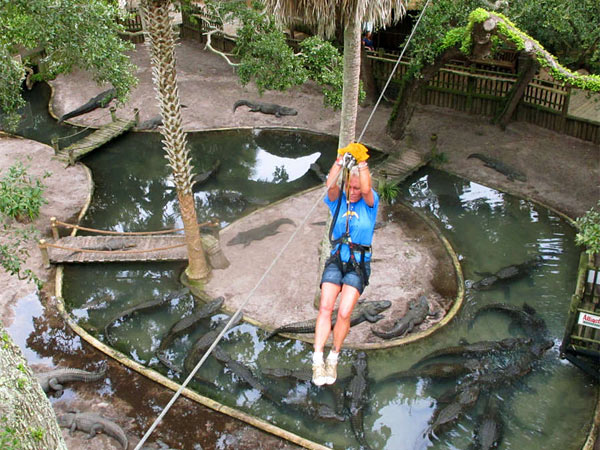Ava Martin, 53, goes zip-lining over an alligator lagoon at the St. Augustine Alligator Farm. It is the only zoo in the world that displays all 23 species of crocodiles. (Brendan Farrington/AP)
