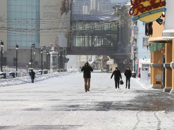 Pedestrians walk along the snow-covered Boardwalk in Atlantic City, N.J., on Friday. The region is bracing for frigid temperatures over the next few days. (AP photo)