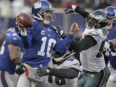 Trent Cole and Darren Howard (right) forced Giants quarterback Eli Manning to throw the ball away on fourth down giving the eagles possession of the ball in the fourth quarter during the Dec. 7, 2008, game at the Meadowlands. (Ron Cortes / Staff Photographer)
