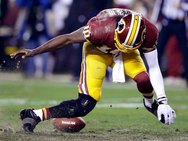 Redskins quarterback Robert Griffin III twists his knee chasing a loose ball during the second half of Washington´s 24-14 wild card loss to the Seahawks. (Richard Lipski/AP)