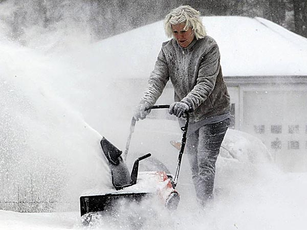 Lynette Johnson snow blows her Springville, New York, driveway in the bitter wind and cold on Monday, Jan. 6, 2014. (Harry Scull Jr./The Buffalo News/AP)