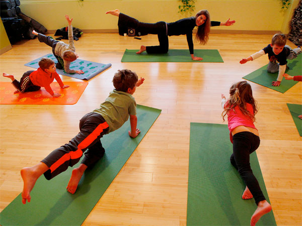Instructor Lauren Robertson guides students (clockwise) Ryan Schaeffer,6, Gabriel Schrieber, 5, Alyiah Brownstein, 5, Zach Brownstein, 8, Reid Reichman, 4, and Aiden Reichaman, 7, into a pose during a Kids class at the Yoga Garden in Narberth. ( MICHAEL S. WIRTZ / STAFF PHOTOGRAPHER ).