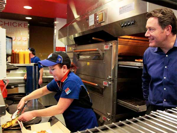 Domino´s Pizza CEO Patrick Doyle keeps a close eye on Katie Ritchie makes a sandwich in Seattle, Washington. (Mark Harrison / Seattle Times / MCT)