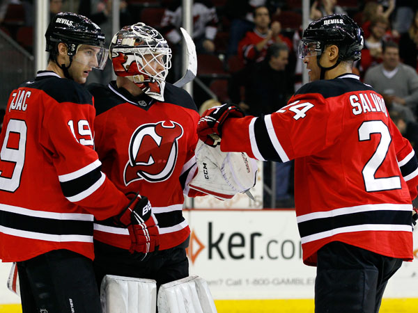 Devils goalie Cory Schneider, center, is congratulated by New Jersey Devils defenseman Bryce Salvador, right, and New Jersey Devils center Travis Zajac after defeating the Dallas Stars in their NHL hockey game Thursday, Jan. 9, 2014, in Newark, N.J. The Devils won 1-0. (Adam Hunger/AP)