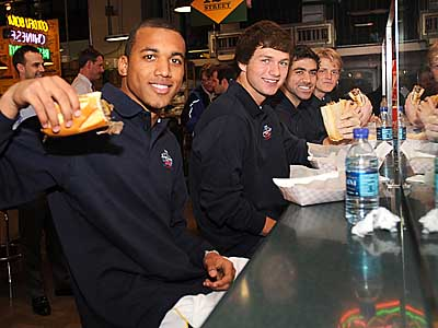 Soccer players Teal Bunbury (left) from Akron, Jack McInerney from the U.S. Under-17 National Team, Austin da Luz from Wake Forest, and Brian Perk from UCLA, try a cheesesteak from Carmen´s in Reading Terminal Market at a press conference in advance of the MLS SuperDraft. (Sharon Gekoski-Kimmel/Staff Photographer)