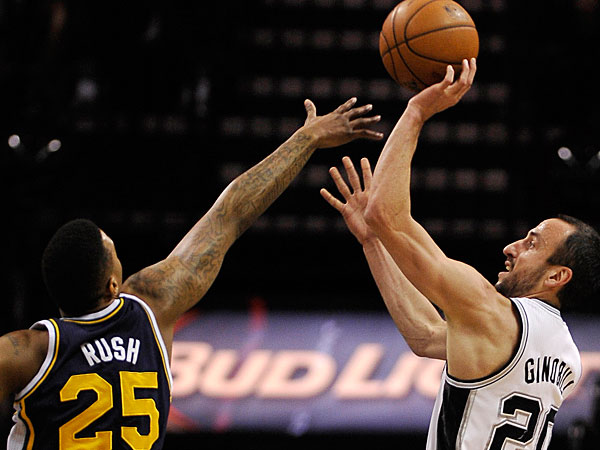 Spurs guard Manu Ginobili, right, of Argentina, shoots over Utah Jazz guard Brandon Rush during the first half of an NBA basketball game, Wednesday, Jan. 15, 2014, in San Antonio. San Antonio won 109-105. (Darren Abate/AP)