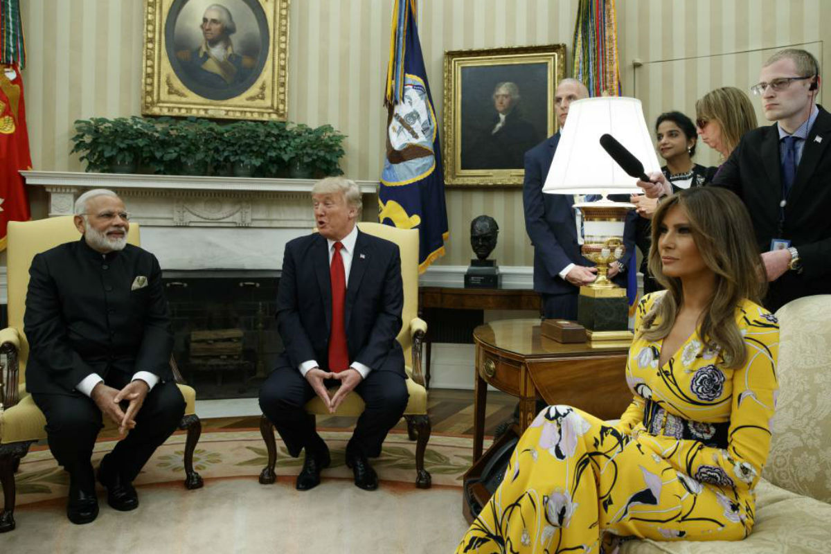 FILE - In this June 26, 2017 file photo, President Donald Trump, accompanied by first lady Melania Trump, meets with Indian Prime Minister Narendra Modi in the Oval Office of the White House in Washington. Melania Trump is wearing a yellow floral Pucci dress.