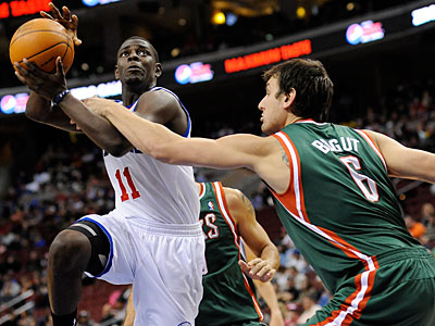 Jrue Holiday drives past Milwaukee Bucks´ Andrew Bogut in the first half. (Michael Perez/AP)