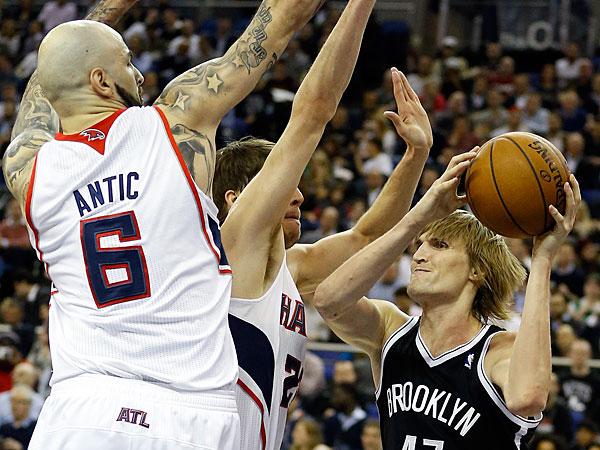The Hawks´ Pero Antic, left, blocks Brooklyn Nets´ Andrei Kirilenko during an NBA basketball game at the O2 Arena in London, Thursday, Jan. 16, 2014. (Kirsty Wigglesworth/AP)