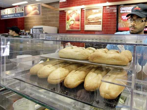 Ra Matthews puts freshly baked hoagie rolls on display at the Wawa.