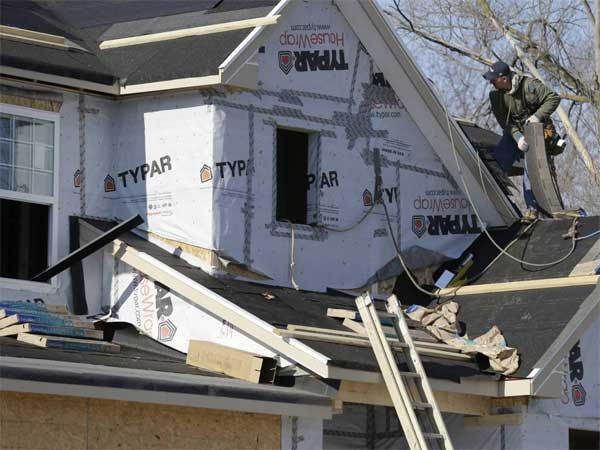 A builder works on the the roof of a new home under construction on Friday, Dec. 27, 2013., in Wilmette, Ill. (AP Photo/Nam Y. Huh)