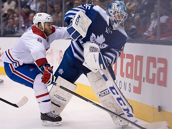Maple Leafs goaltender Jonathan Bernier tries to clear the puck under pressure from Montreal Canadiens left winger Brandon Prust during the third period of an NHL hockey game Saturday, Jan. 18, 2014, in Toronto. (AP Photo/The Canadian Press, Frank Gunn)