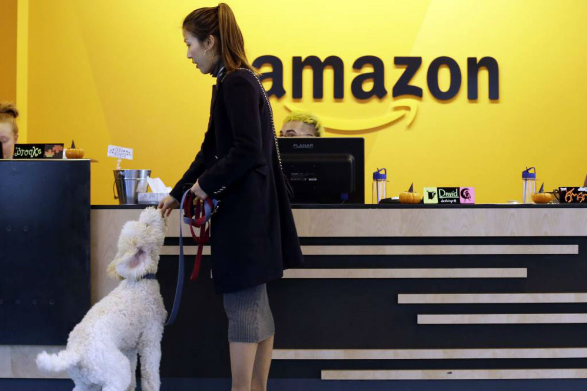 FILE - In this Wednesday, Oct. 11, 2017, file photo, an Amazon employee gives her dog a biscuit as the pair head into a company building, where dogs are welcome, in Seattle. Amazon announced Thursday, Jan. 18, 2018, that it has narrowed its hunt for a second headquarters to 20 locations, concentrated among cities in the U.S. East and Midwest. Toronto made the list as well, keeping the company´s international options open.