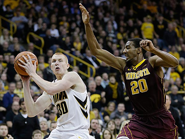 Iowa forward Aaron White drives to the basket ahead of Minnesota guard Austin Hollins. (Charlie Neibergall/AP)
