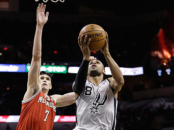 The Spurs´ Patty Mills scores past the Bucks´ Ersan Ilyasova. (Eric Gay/AP)