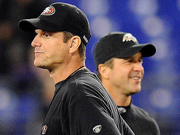 49ers head coach Jim Harbaugh, foreground, stands alongside his brother, Ravens head coach John Harbaugh, before an NFL football game. (Nick Wass/AP file photo)