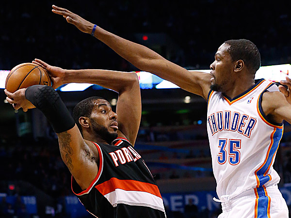 Thunder forward Kevin Durant defends Trail Blazers forward LaMarcus Aldridge. (Sue Ogrocki/AP)