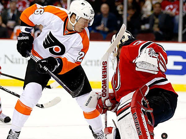 Devils goalie Martin Brodeur blocks a shot by Flyers left wing Ruslan Fedotenko. (Julio Cortez/AP)