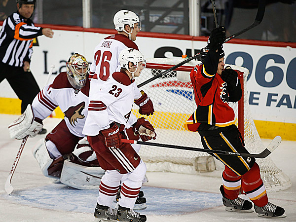 Coyotes goalie Mike Smith, Michael Stone and Oliver Ekman-Larsson look on as the Flames´ Lance Bouma celebrates his goal during the second period. (Jeff McIntosh/The Canadian Press/AP)