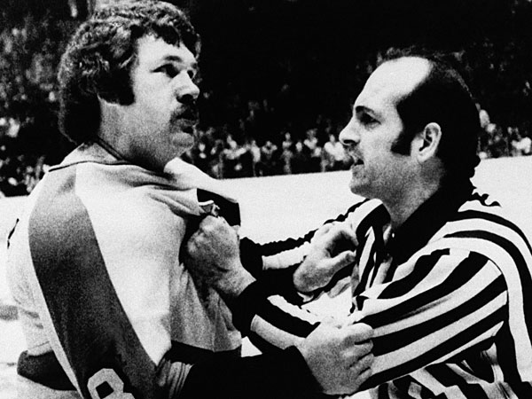 "Dave ""The Hammer"" Schultz, of the Philadelphia Flyers, is restrained by a linesman as he tries to continue a fight that had been halted. Schultz was the most penalized man in the National Hockey League in 1975, mostly due to fighting. (Rusty Kennedy/AP file)"