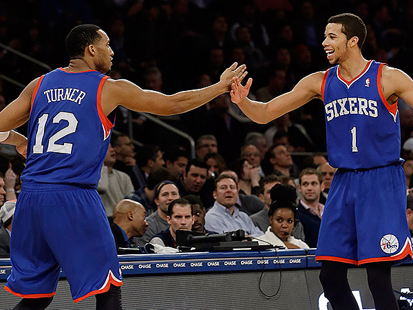 Evan Turner celebrates with Michael Carter-Williams after hitting a three against the Knicks on Wednesday. (Frank Franklin II/AP)