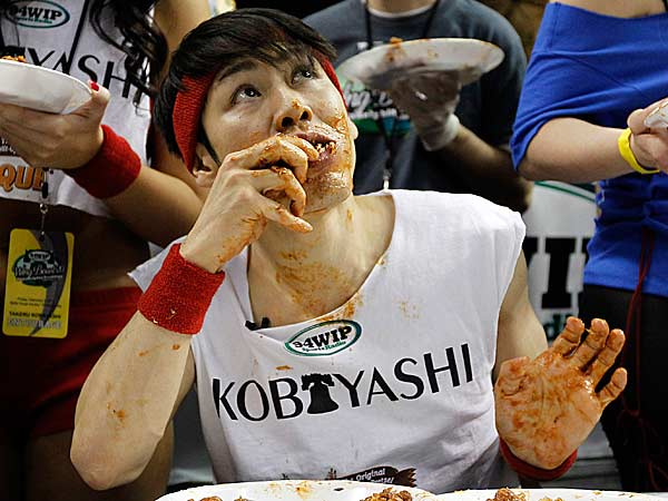 Japanese competitive eater Takeru Kobayashi looks up as he eats chicken wings during SportsRadio WIP's Wing Bowl 2012 eating contest Friday, Feb. 3, 2012 in Philadelphia. Kobayashi won by eating 337 wings. (Alex Brandon/AP file)