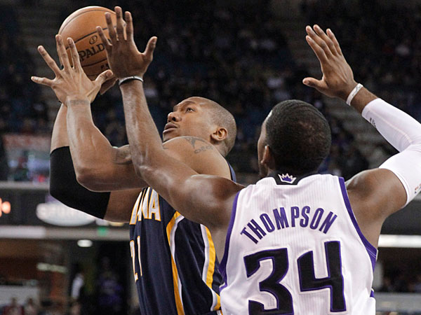 Pacers forward David West, left, goes to the basket against Sacramento Kings forward Jason Thompson during the first quarter of an NBA basketball game in Sacramento, Calif., Friday, Jan. 24, 2014. (Rich Pedroncelli/AP)