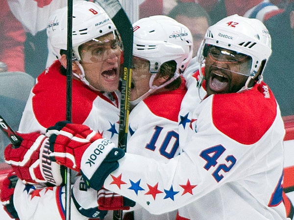 The Capitals´ Alex Ovechkin, left, celebrates with teammates Martin Erat, center, and Joel Ward after Ovechkin scored against the Montreal Canadiens during the second period of an NHL hockey game in Montreal, Saturday, Jan. 25, 2014. (AP Photo/The Canadian Press, Graham Hughes)