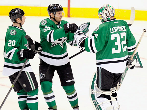 Stars center Cody Eakin (20) and defenseman Sergei Gonchar (55) celebrate with goalie Kari Lehtonen (32) after their 3-0 win over the Pittsburgh Penguins in an NHL hockey game, Saturday, Jan. 25, 2014, in Dallas. (Matt Strasen/AP)