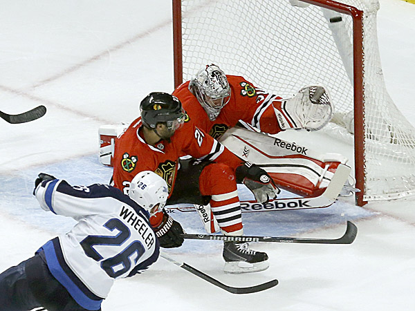 Jets right wing Blake Wheeler shoots and scores past Blackhawks defenseman Johnny Oduya and Corey Crawford. (Charles Rex Arbogast/AP)