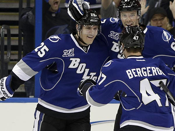 Tampa Bay Lightning defenseman Matt Carle (25) celebrates with left wing Benoit Pouliot (67) and defenseman Marc-Andre Bergeron (47) after scoring against the Ottawa Senators during the first period of an NHL hockey game Friday, Jan. 25, 2013, in Tampa, Fla. (AP Photo/Chris O´Meara)