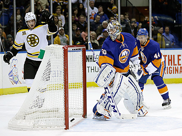 The Bruins´ Loui Eriksson celebrates after he scores a goal past Islanders goalie Kevin Poulin while Calvin de Haan looks on. (Seth Wenig/AP)