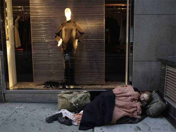 A destitute man sleeps on the sidewalk under a holiday window at Blanc de Chine in New York. A Gallup poll found two-thirds of Americans are dissatisfied with the nation´s distribution of wealth. (AP Photo/Mark Lennihan, File)