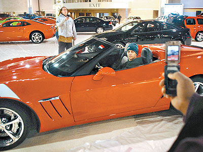 Carpenter Anthony Lucia of Blackwood, N.J., poses in a 2010 Corvette GS Convertable ($75,365.00) for a cell phone camera photo by fellow carpenter Terry Higgins,  of West Oak Lane, in the Pennsylvania Convention Center Thursday in preparation for the opening of the Auto Show. (Tom Gralish / Staff Photographer)