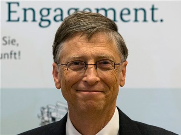 Bill Gates, founder of the software company Microsoft, poses for the media prior to a press conference after a meeting with German Development Aid Minster Dirk Niebel, unseen, in Berlin, Germany, Tuesday, Jan. 29, 2013. Slogan in the background reads ´Commitment´. (AP Photo/Michael Sohn)