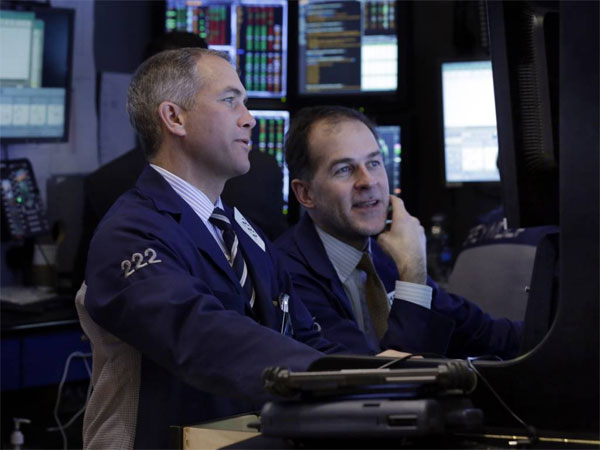 Traders work in their booth on the floor of the New York Stock Exchange. The stock market closed out its best week of the year Friday as investors focused on earnings and brushed off another weak economic report.. (AP Photo/Richard Drew)