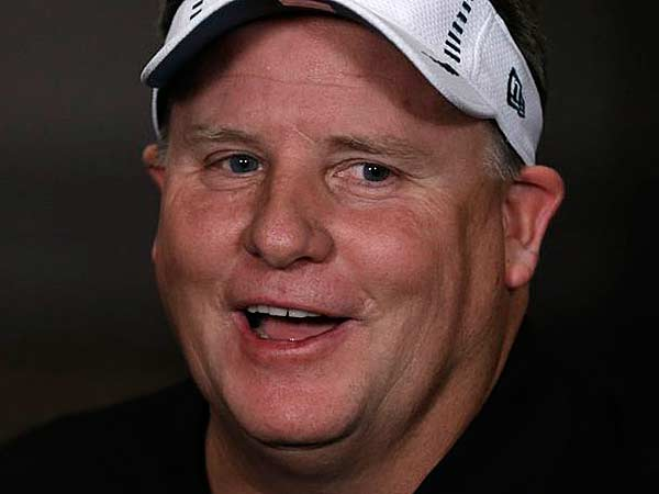 Chip Kelly wears a visor given to him to wear by a reporter during a television interview after a press conference at the team´s NFL football training facility, Thursday, Jan. 17, 2013, in Philadelphia. (Matt Rourke/AP)