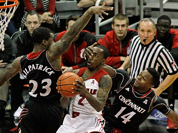 Louisville guard Russ Smith (2) gets a hand in the face from Cincinnati´s Ge´Lawn Guyn (14) on this shot attempt inside in a NCAA college basketball game in Louisville. Ky., Thursday, Jan. 30, 2014. At right is Cincinnati´s Sean Kilpatrick (23). (Garry Jones/AP)