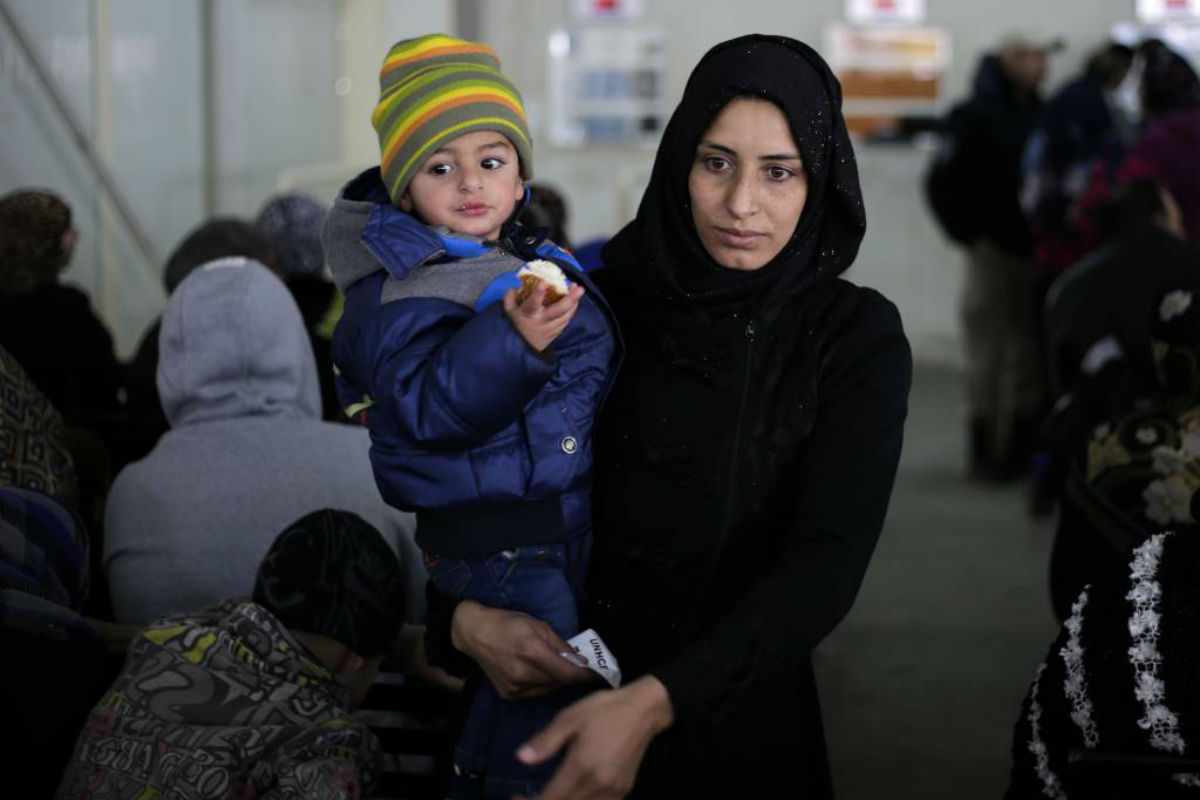 A Syrian boy eats bread as waits in line with his mother as hundred of Syrian families wait to register at the United Nations High Commissioner for Refugees headquarters, in Beirut, Lebanon, Monday, Jan. 30, 2017. By executive order, U.S. President Donald Trump imposed a 90-day ban, Friday, that affects travel to the U.S. by citizens of Iraq, Syria, Iran, Sudan, Libya, Somalia and Yemen and puts an indefinite hold on a program resettling Syrian refugees.