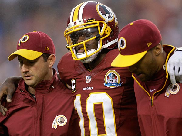 Washington Redskins quarterback Robert Griffin III is helped off the filed after an injury during the second half of an NFL football game against the Baltimore Ravens in Landover, Md., Sunday, Dec. 9, 2012. (AP Photo/Patrick Semansky)