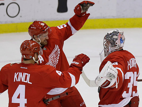 Red Wings goalie Jimmy Howard (35) is congratulated by Jakub Kindl (4), of the Czech Republic, and Niklas Kronwall (55), of Sweden, after Detroit´s 4-3 win over the Washington Capitals in a shootout in an NHL hockey game in Detroit, Friday, Jan. 31, 2014. (Carlos Osorio/AP)