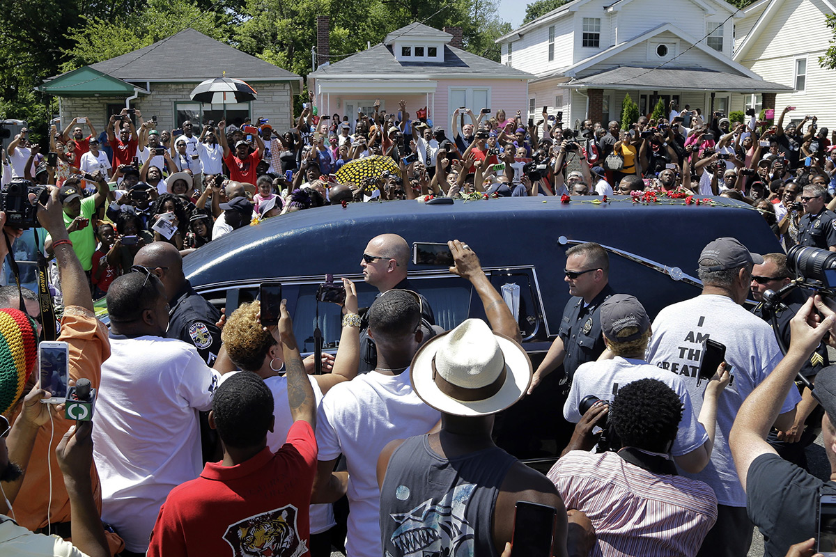 The hearse carrying the body of Muhammad Ali passes in front of his boyhood home (top center) during his funeral procession in Louisville, Ky., on June 10, 2016.
