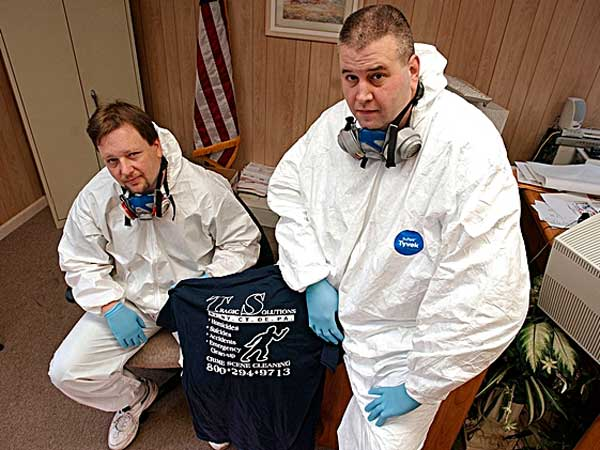 FILE PHOTO: Timothy Carroll, left, and Thomas Rohling co-owners of Tragic Solutions,  pose in protective biohazard coveralls at their office in Newark, N.J., Thursday, Dec. 16, 2004.  (AP Photo/Mike Derer)
