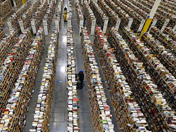 In this Monday, Dec. 2, 2013, file photo, an Amazon.com employee stocks products along one of the many miles of aisles at an Amazon.com Fulfillment Center in Phoenix. (AP Photo/Ross D. Franklin, File)